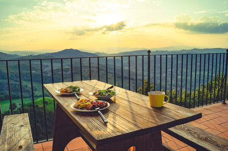 fresh breakfast with salads on a wooden table with the view of the mountains in the morning