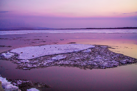 cracked ice on a river in spring time during the sunset in pink and lilac colors Imagens