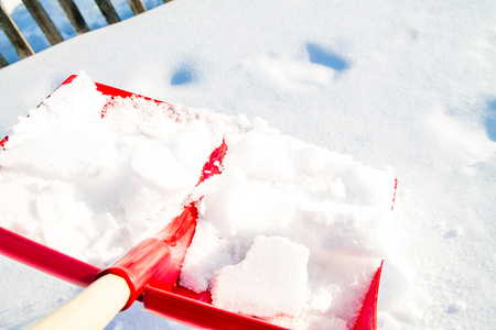 Close up of a big red plastic showel in the process of removing the snow in winter