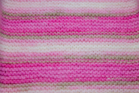 Pink, white and light brown striped knitted texture background