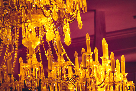 large yellow chandelier with candles on a ceiling in a theater