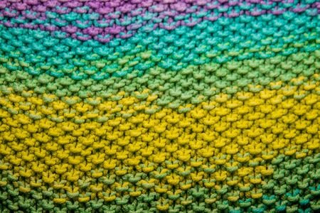 a multicolor yellow, green, orange and purple horizontal knitted pattern background Stock fotó