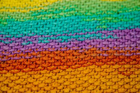 a multicolor yellow, green, orange and purple horizontal knitted pattern background Foto de archivo