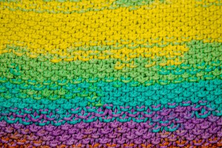 a multicolor yellow, green, orange and purple horizontal knitted pattern background Фото со стока