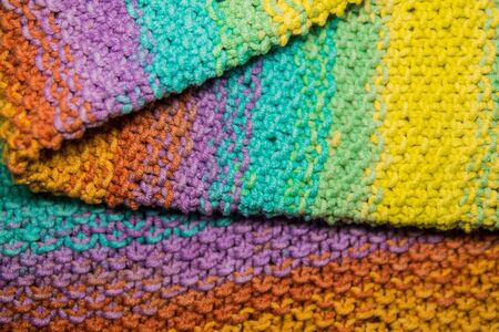 a multicolor yellow, green, orange and purple horizontal knitted folded fabric pattern background Banque d'images