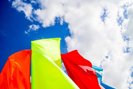 Colorful red and yellow flags waving on the bright blue sky background with white fluffy clouds