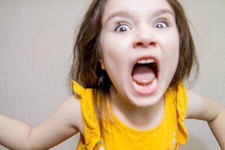 Gracioso desenfocado retrato de cerca de una pequeña niña enojada agresiva gritando sobre fondo blanco.