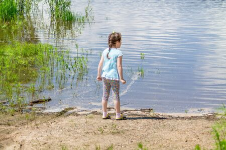 Young girl standing near a river and watching the water