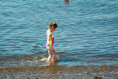 a Little girl in a swimsuit bathing in the sea in summer, making a splash and running in water