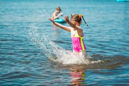 Little girl in a swimsuit bathing in the sea in summer, making a splash and running in water