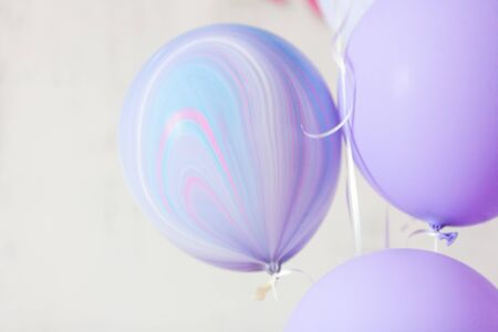 Flying purple and violet balloons on a light gray background while celebration. Birthday background with ballons. Imagens - 132165674