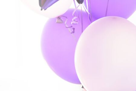 Flying purple and violet balloons on a light gray background while celebration. Birthday background with ballons. Imagens