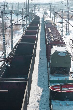a vertical banner of rail cars loaded with coal being transported from nearby mines to power plants in winter