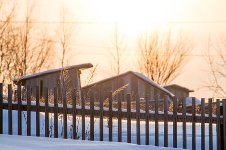 Beautiful cozy rural country winter landscape with rural wooden house on background and wooden fence in front of it during the sunset. Outdoor recreation concept.