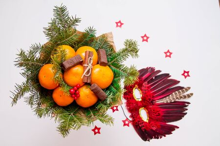 Red carnival mask made of feathers and christmas bouquet with wild wood berries, chocolates, tangerines and fur-tree branches in craft paper. Isolated on white background