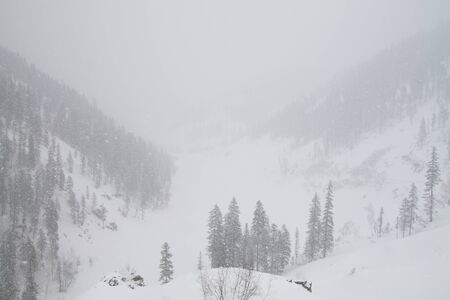 Winter landscape with heavy snowfall in mountains and gray sky
