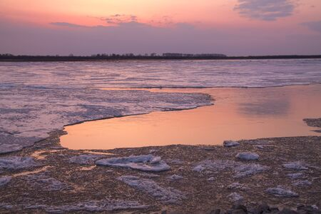 picturesque colorful ice drift on a calm wide river during the pink sunset