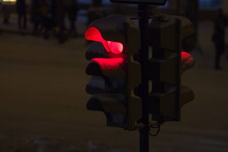 close up of red traffic light during the snowfall in the evening