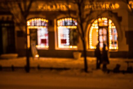 a Defocused view of the city street with windows framed with Christmas lights. Night time. Pedestrians walking on the sidewalk