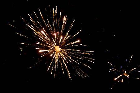 Feux d'artifice dorés sur fond noir, feux d'artifice explosent, fond de feux d'artifice, spectacle de lumière, gros plan