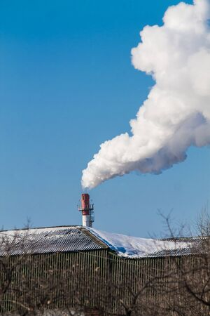 Industrial pipe with dense white smoke on the blue sky background