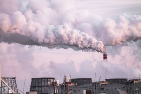 industrial chimneys with heavy smoke causing air pollution as an ecological problem on the pink sunset sky background Stock Photo