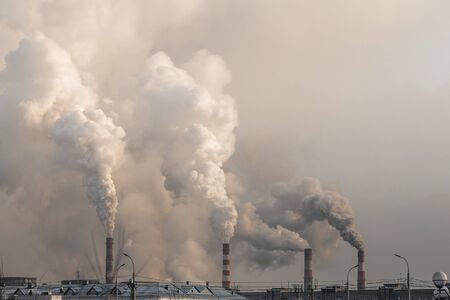 industrial chimneys with heavy smoke causing air pollution on the gray sky background