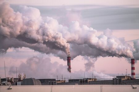 industrial chimneys with heavy smoke causing air pollution as an ecological problem on the pink sunset sky background