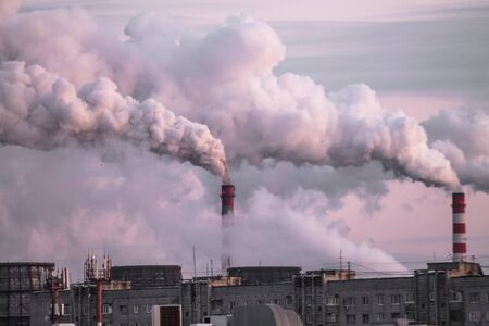 industrial chimneys with heavy smoke causing air pollution as an ecological problem on the pink sunset sky background Zdjęcie Seryjne