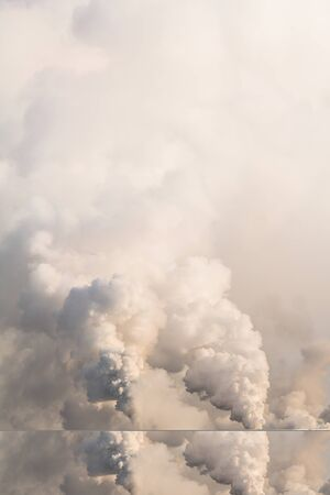 Vertical banner of industrial chimneys with heavy smoke causing air pollution on the gray sky background
