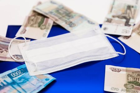 White medical protective mask laying on Russian rubles banknotes on dark blue background as symbol of higher prices for respiratory protection from coronavirus Covid19