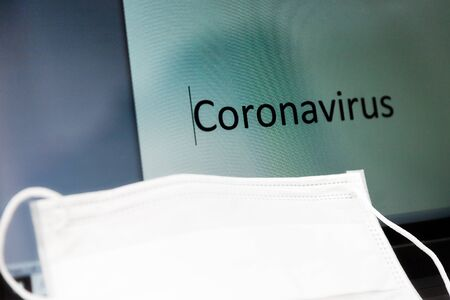 word Coronavirus written on LED monitor of a notebook with a protective medical mask on a keyboard