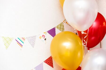 Festive decorations with white and golden balloons and colorfulflags on a white wall background with copy space 免版税图像