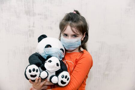 sad unhappy Little girl wearing protective mask with panda toy in her hands wearing medical mask on white background