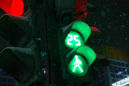Green light traffic light on a dark background with walking pedestrian at night during snowfall in winter