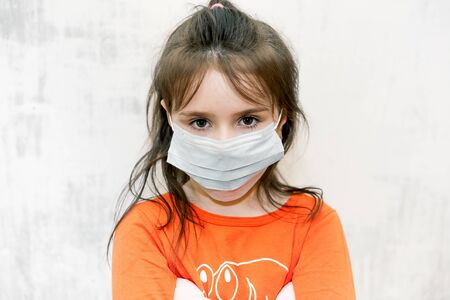 Sad unhappy little girl on white  wearing a protective medical mask and sitting in isolation on quarantine