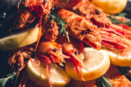 bunch of big cooked red shrimps , king prawns, crab legs, lemons and rosemary branches made as a healthy food gift full of protein