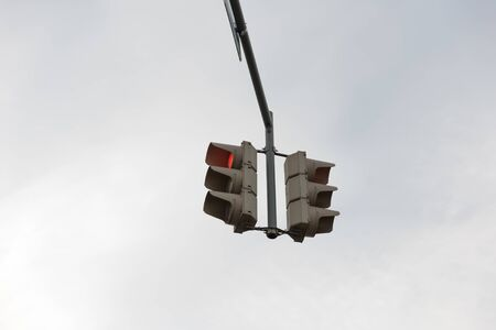 red traffic light with standing person symbol in the city street on grey sky background