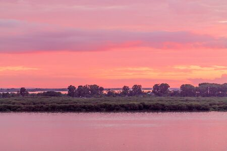 river and meadows landscape during pink summer Sunset with pink and purple clouds 免版税图像