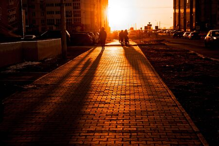 sidewalk with walking people after work in back light during the sunset