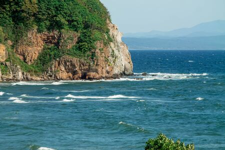 seascape, a beautiful view of the rocky cliff in the sea with mountains on the horizon 免版税图像