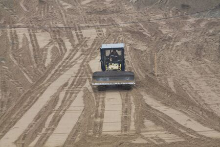 A yellow bulldozer on a sandy surface on construction site territory 免版税图像