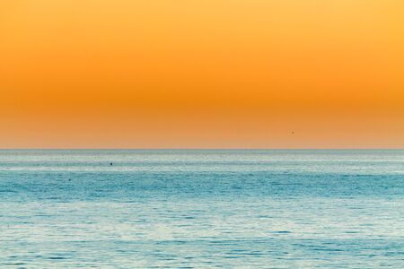 the orange Sunset over the calm blue ocean 免版税图像