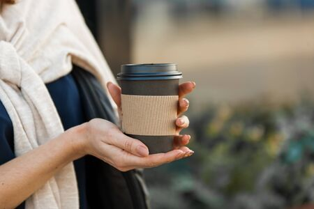 beautiful woman's hands with a cup of coffeen in craft paper in the street 免版税图像