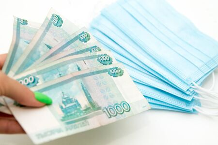 womans hands holding a hip of russian 1000 rubles banknotes in front of blue medical masks as expenses concept during coronavirus covid19 pandemic