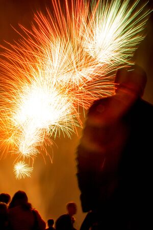 Silhouettes of people watching yellow, white and red fireworks in night sky on Independence Day