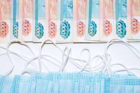 blue medical masks lying opposite lots of russian rubles banknotes as expenses concept during the coronavirus covid19 pandemic