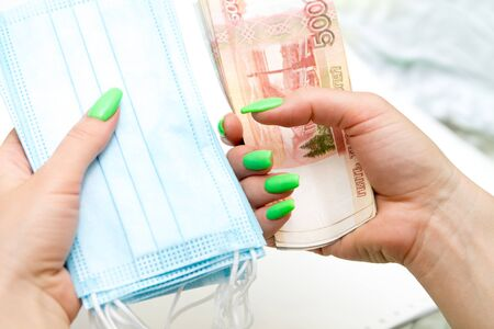 womans hands holding a hip of blue medical masks and a hip of russian rubles banknotes as expenses concept during the coronavirus covid19 pandemic