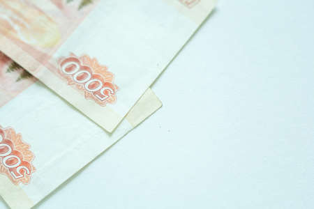 Russian 5000 rubles currency money on white background with copy space asa symbol of business and prospeity. Focus on number 5000 on red banknote
