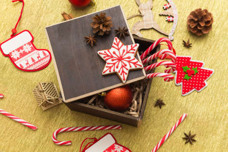 Christmas gift composition flatlay with festive decoration, gingerbread and sugar cane candies in a dark brown box on golden background. Happy New Year 2021